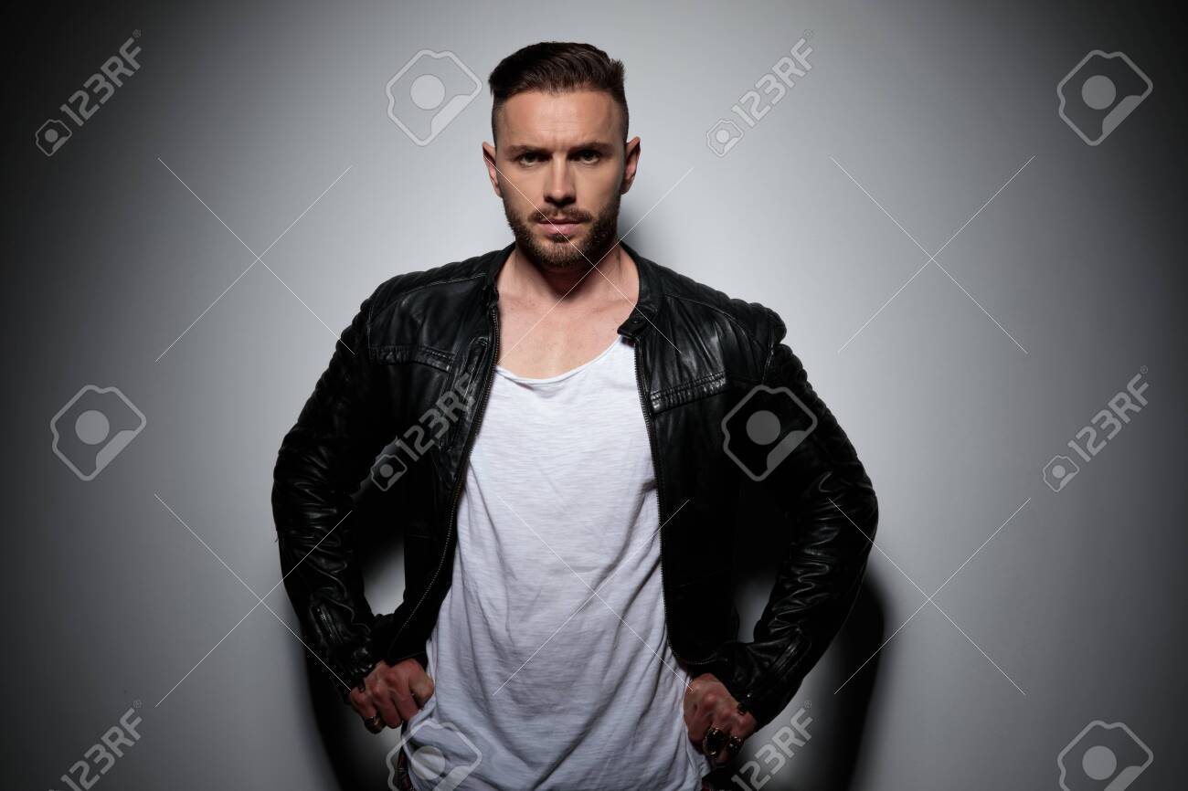 Tough young man adjusting his pants and looking forward while wearing a black leather jacket, standing on gray studio background - 133299719