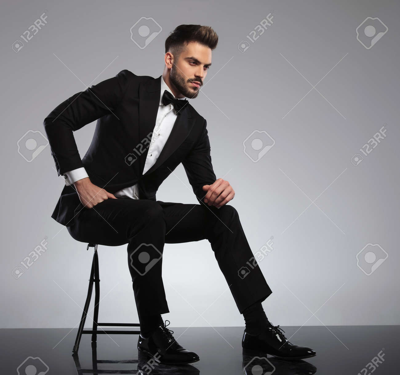 Upset groom frowning and looking away while wearing tuxedo, sitting on a chair on gray studio background - 138287304
