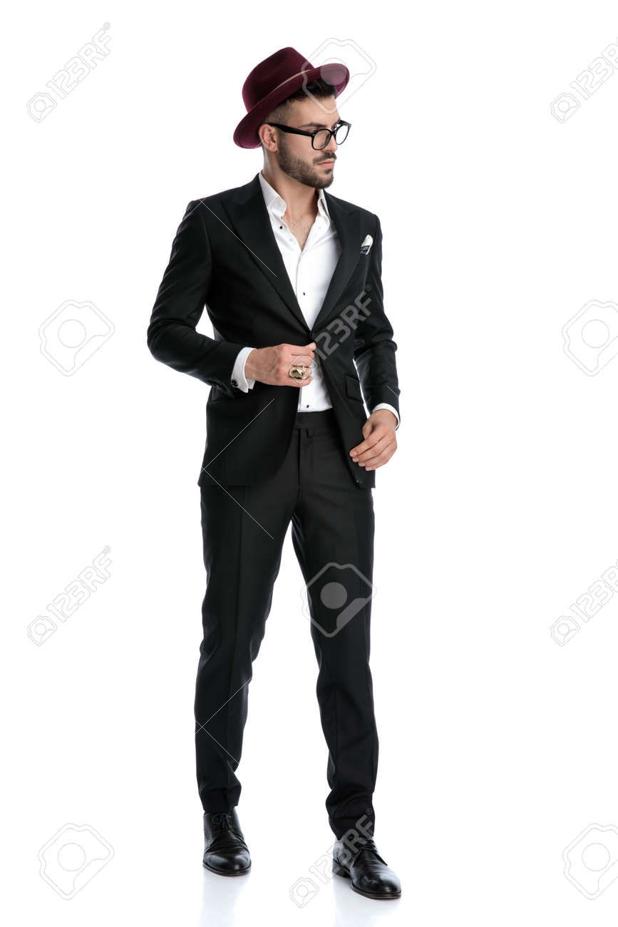 side view of a charming formal business man wearing burgundy hat standing and looking aside while fixing jacket serious against white studio background - 139295181