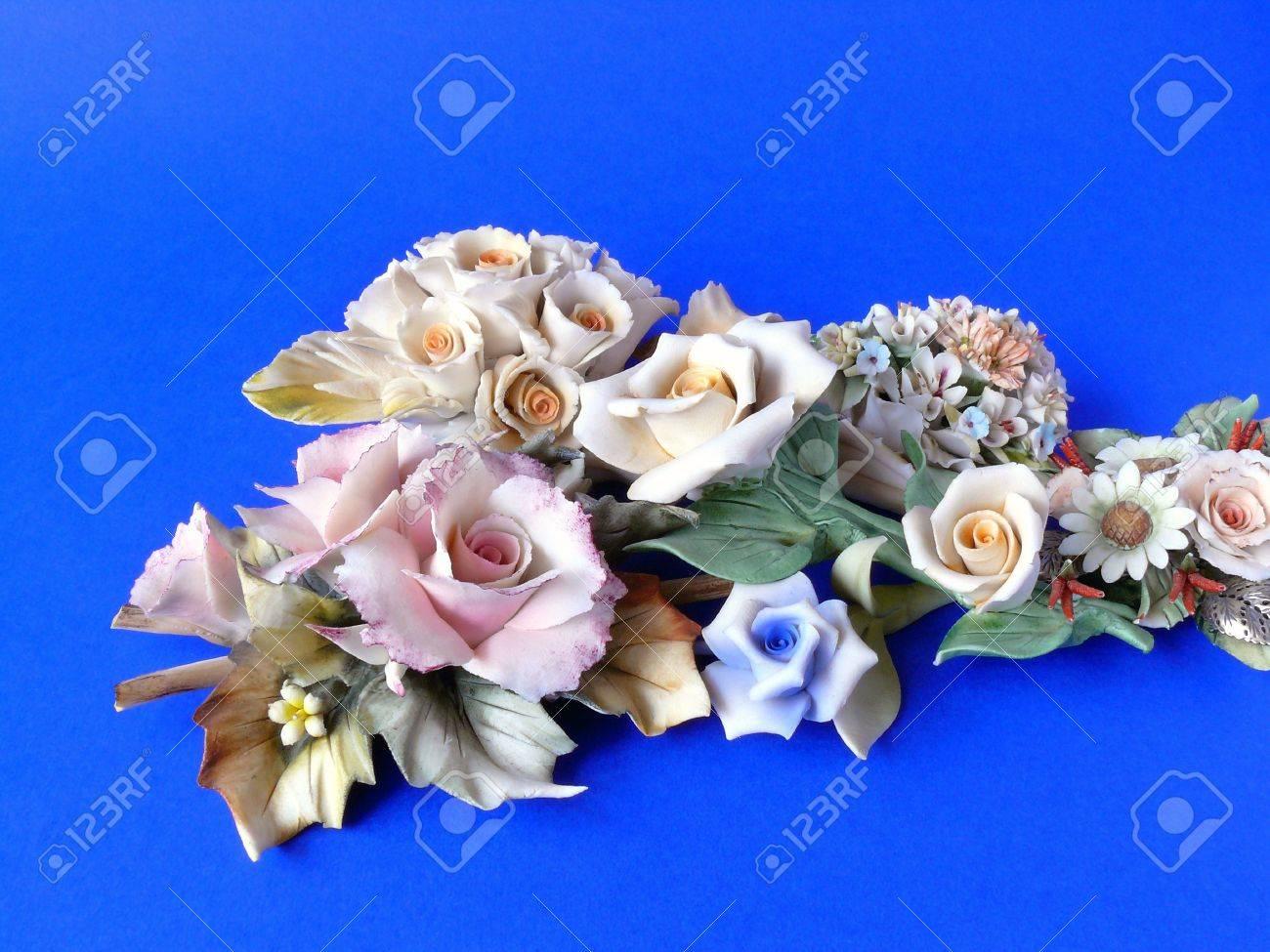 Bunch of ornamental ceramic flowers (like Capodimonte) isolated on blue Standard-Bild - 4464834