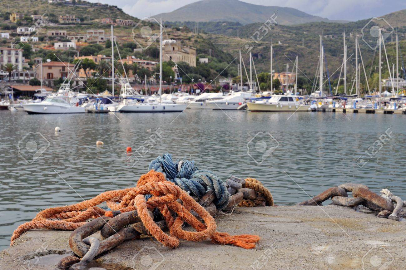 Metal ship mooring and ropes closeup with Marina of Camerota harbor in the background, Italy Stock Photo - 5280247