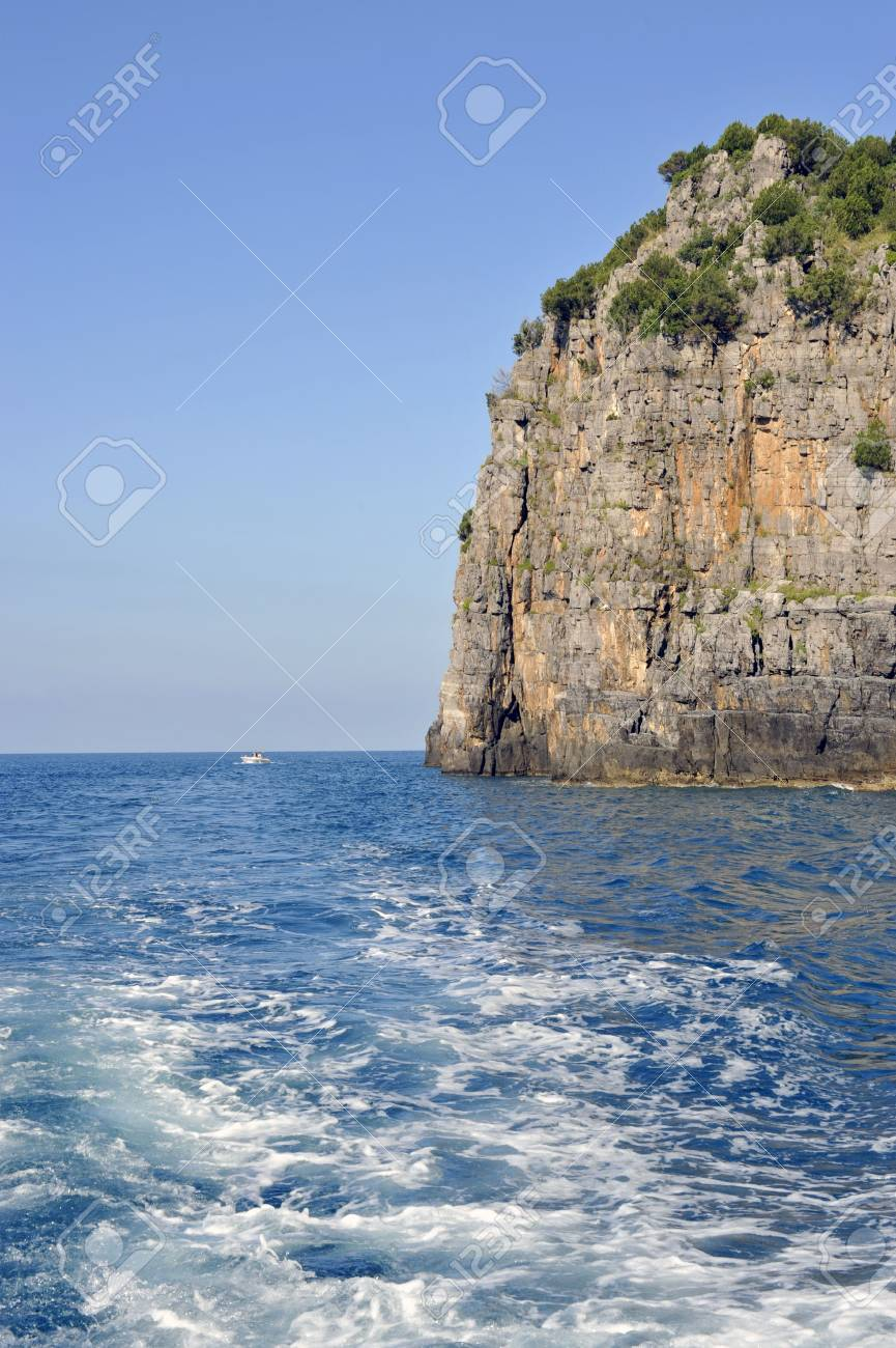 Wake of a boat crossing a sheer rock along Palinuro seacoast, Italy Stock Photo - 5562229