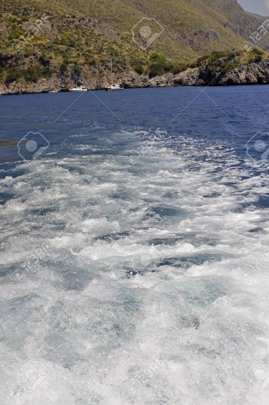 Boat foamy wake along seacoast (vertical) Stock Photo - 5562346