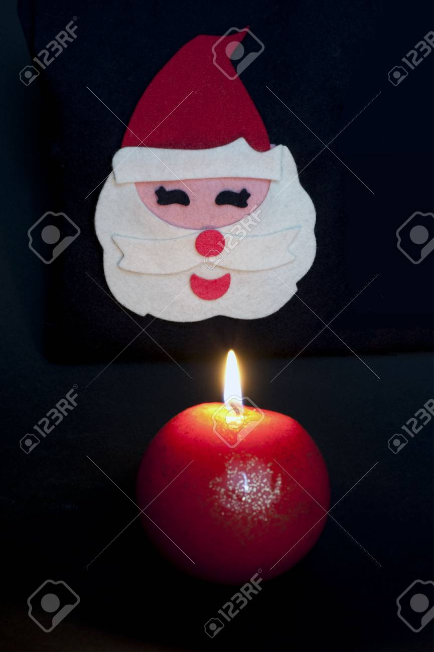 Fabric Santa claus figurine with ball-shaped lighted up candle on black background Stock Photo - 6001350