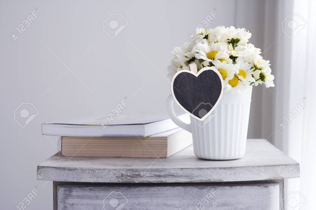Fresh Daisy Flowers In White Cup With Blank Wood Heart Stock Photo