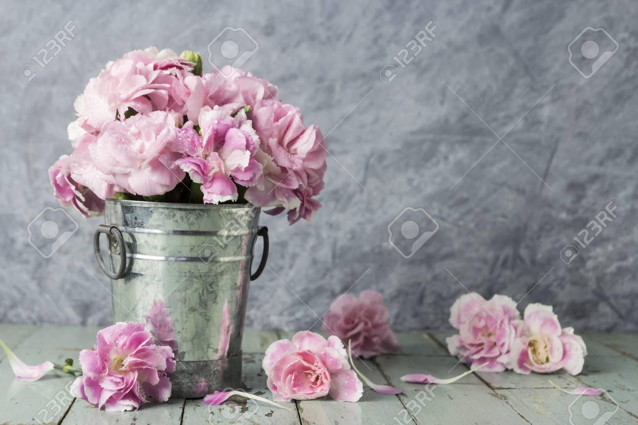 Pink carnation flowers in zinc bucket on old wood - 68442606