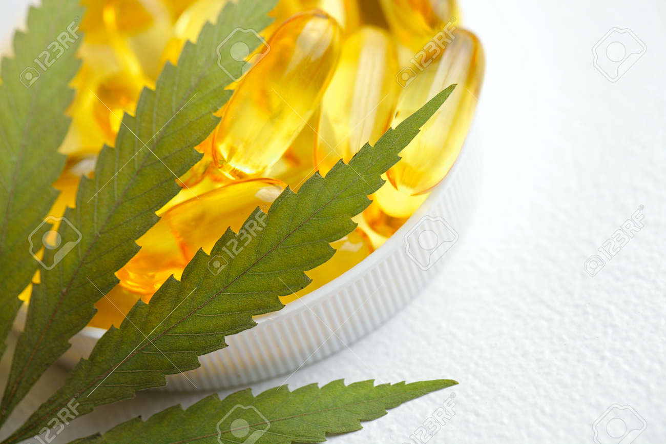 Cannabis CBD capsules are a medical cannabis product with leaves, CBD hemp oil capsules, on white background with copy space - 169732306