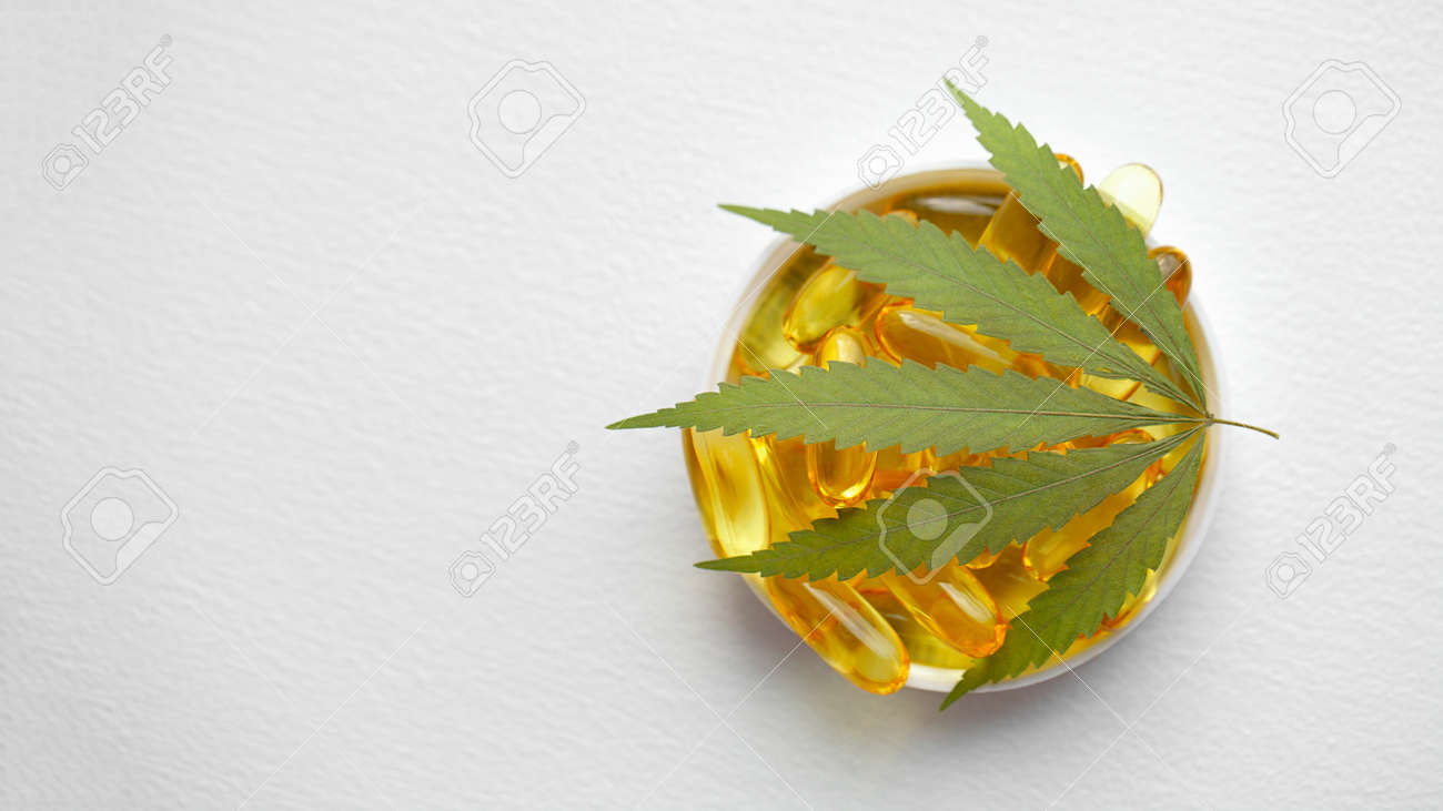 Cannabis CBD capsules are a medical cannabis product with leaves, CBD hemp oil capsules, on white background with copy space - 169732235