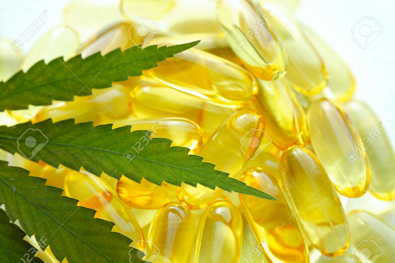 Cannabis essential oil capsules on white background. CBD oil capsules and hemp leaves - 169732218
