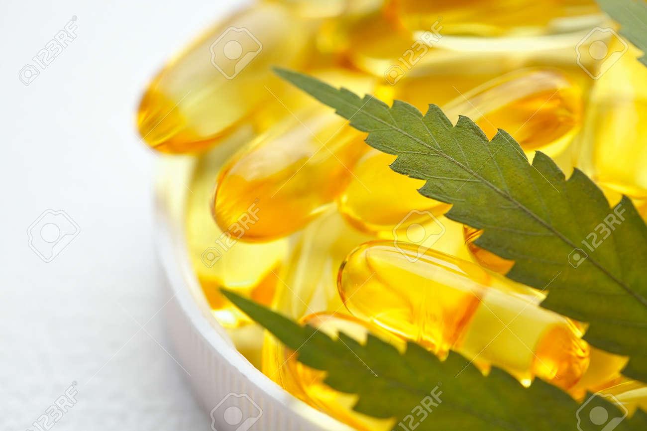 CBD oil capsules and hemp leaves. Macro close up of capsules of biological and ecological hemp plant herbal pharmaceutical cbd oil - 169732223