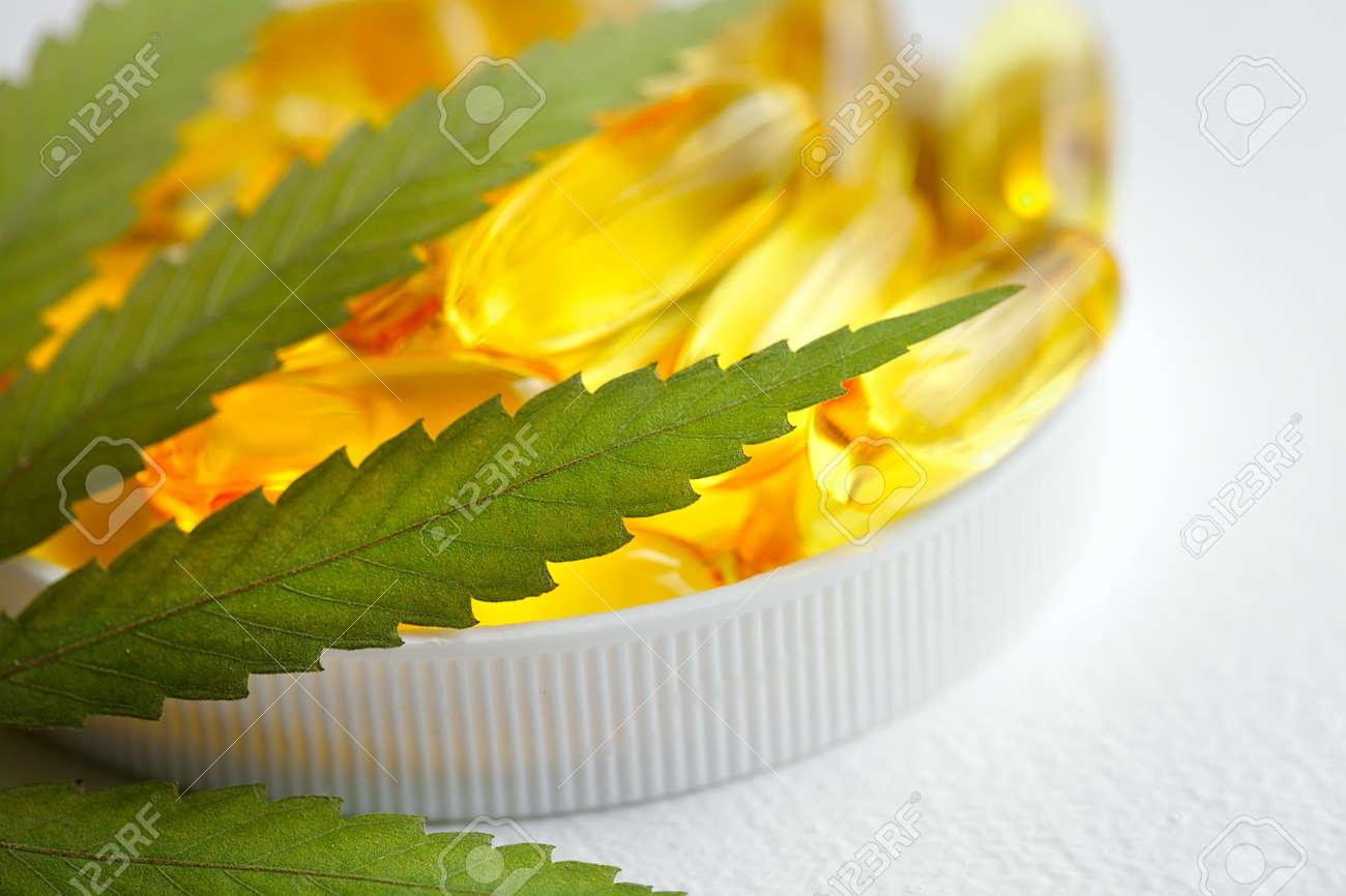 CBD oil capsules and hemp leaves. Macro close up of capsules of biological and ecological hemp plant herbal pharmaceutical cbd oil - 169732097