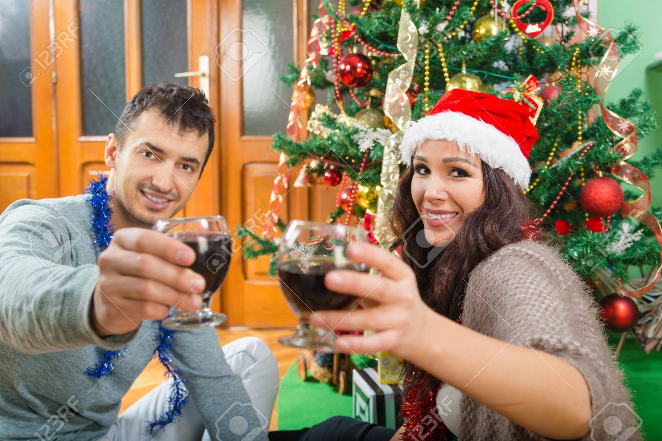 Home By Christmas.Attractive Couple Enjoying Christmas Time Drinking Wine Celebrating