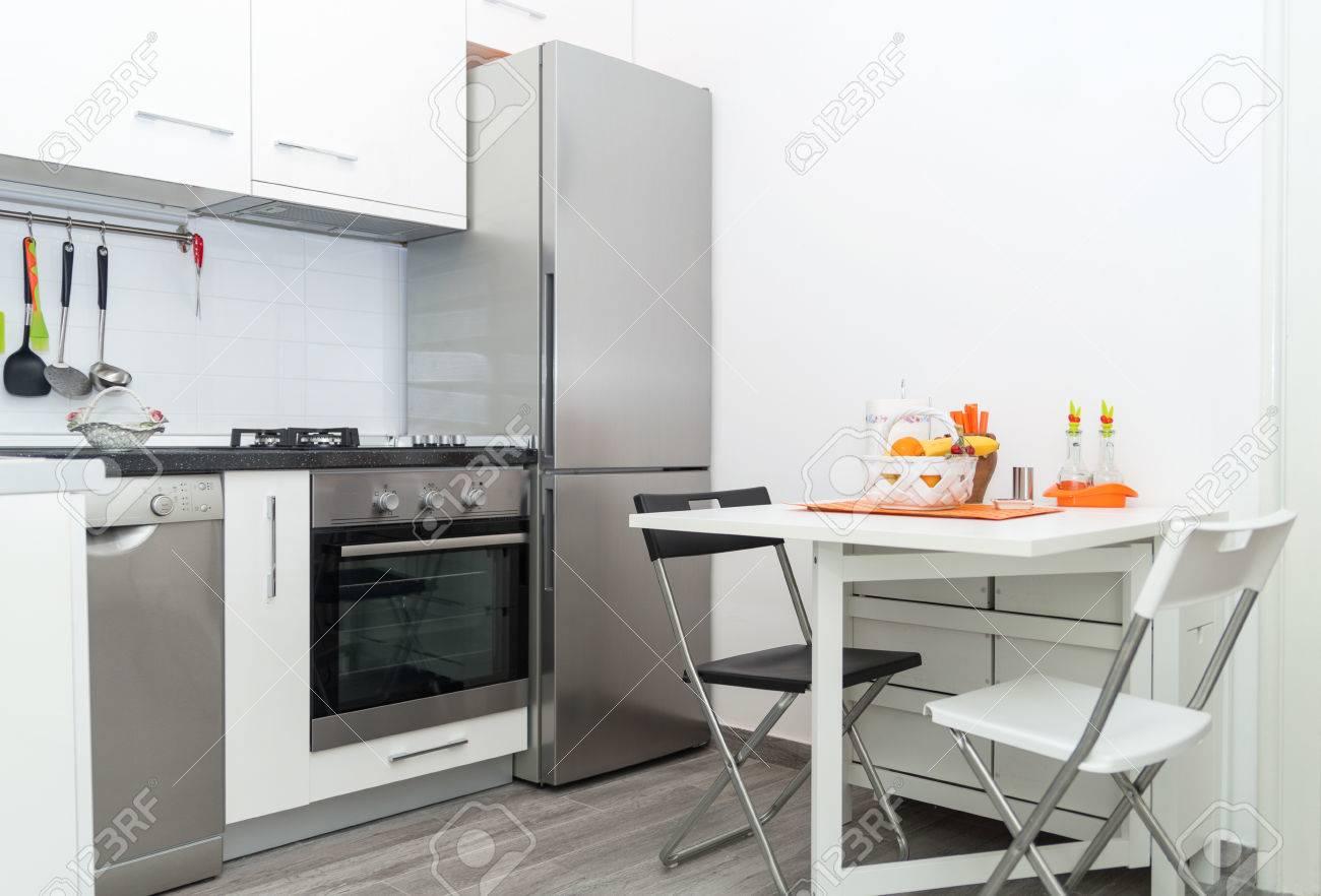 Interior of Small White Kitchen with Fresh Fruit Basket on White..