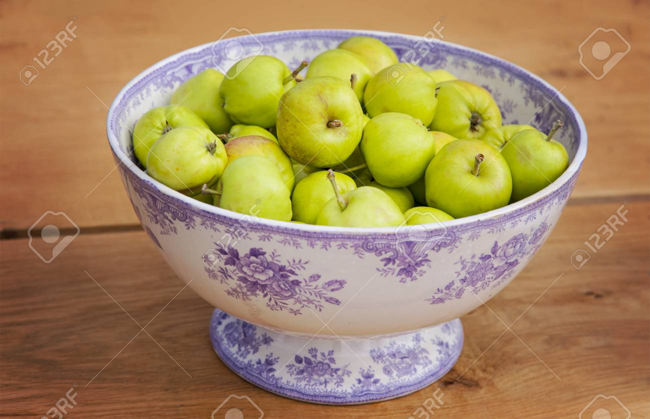 image of an ornate bowl full of ripe green apples stock photo