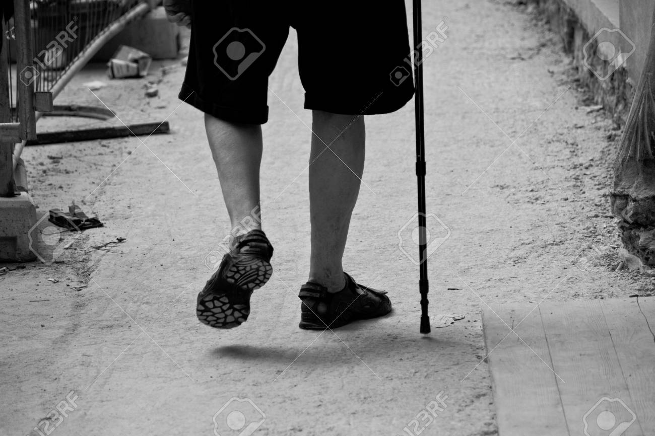 Elderly man walking with the aid of the stick Stock Photo - 7453818