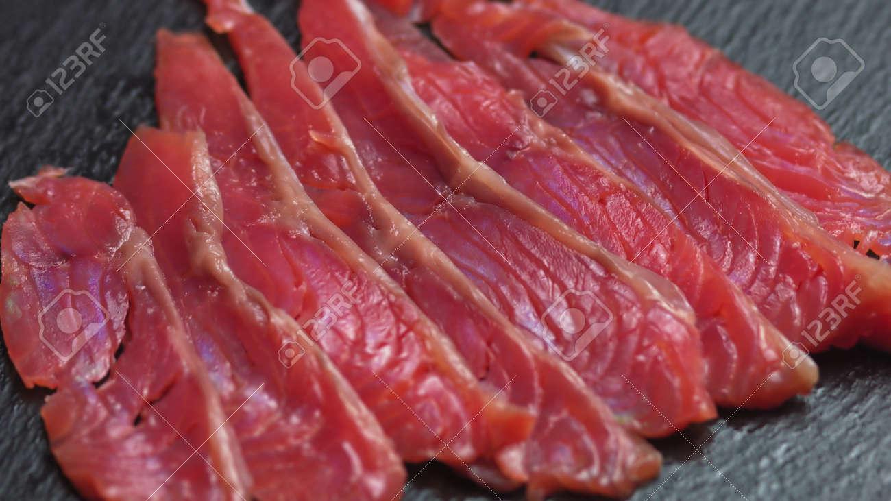 Close up shot of smoothly rotating salmon, Sushi cooking process - Philadelphia, burning fire smoking fresh raw red tuna salmon eel - 157347618