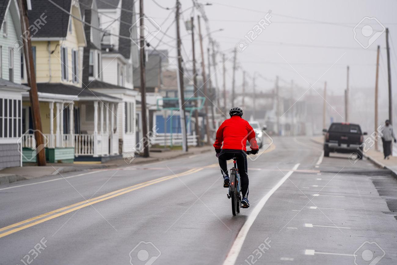 Hampton Beach, NH, USA - December 12, 2020: Man with a red jacket riding a bike in Long Sands Beach Maine - 161760948