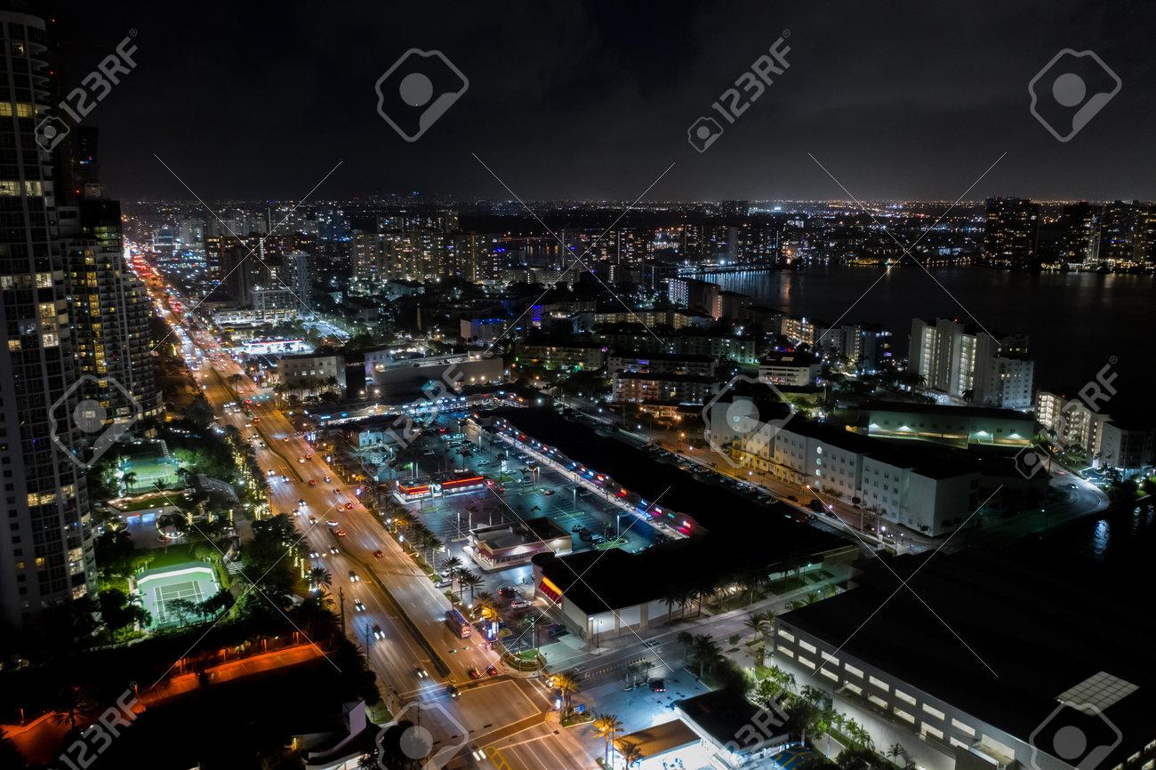 Shopping plaza strip mall night aerial photo - 161711315