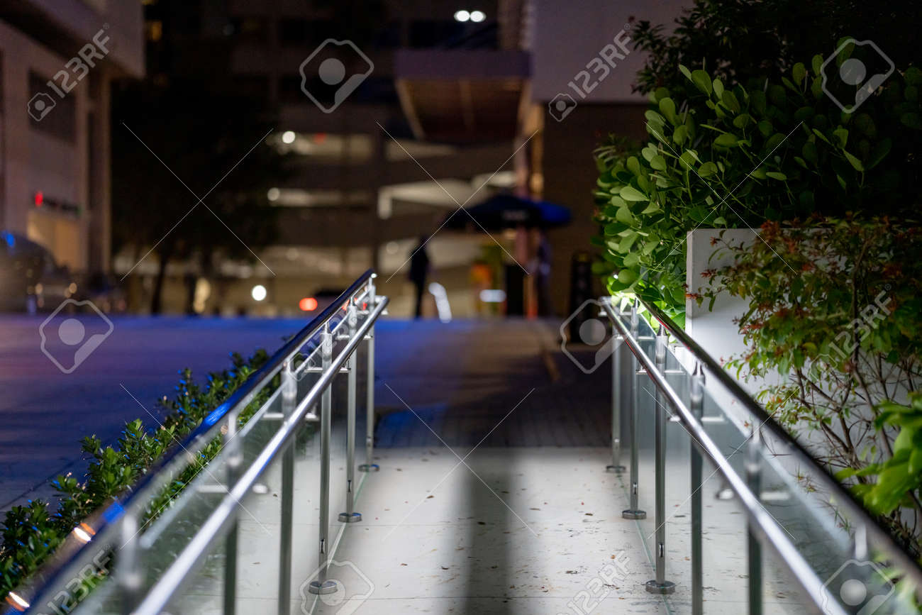 Metal railing to a business building at night - 171574508