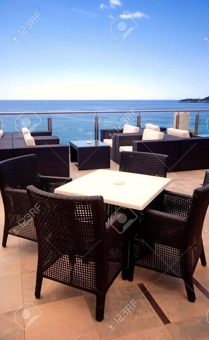 Sillones De Mimbre En El Salón Terraza Con Vistas Al Mar En Un Complejo De Lujo
