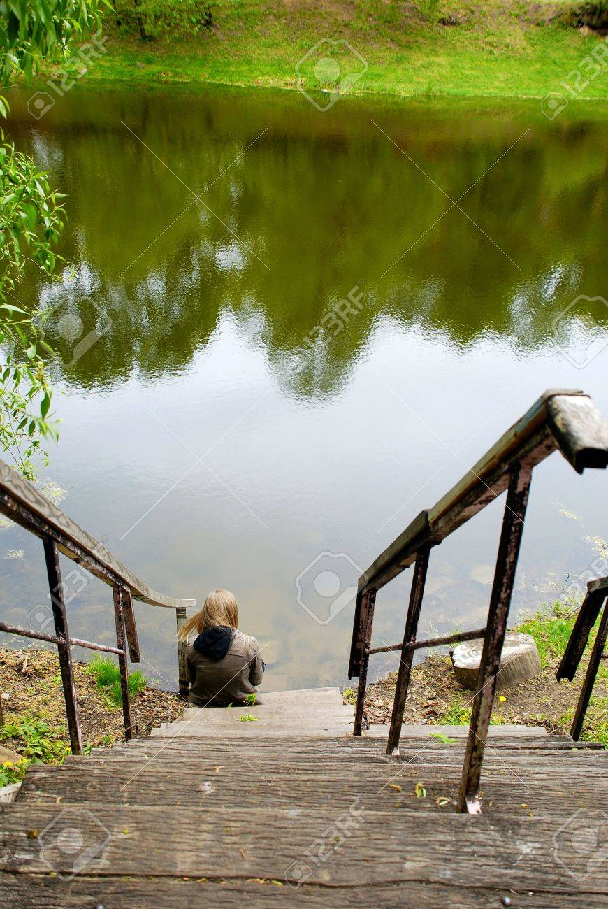 Young Woman Sitting Alone On Old Wood Steps At Summer Pond Coast