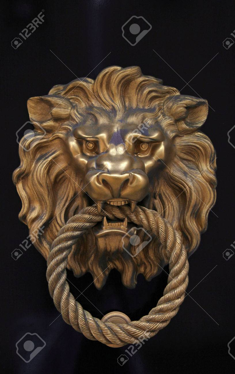 Antique Door Knob In The Shape Of Brass Lion On Brown Wood Background Stock  Photo