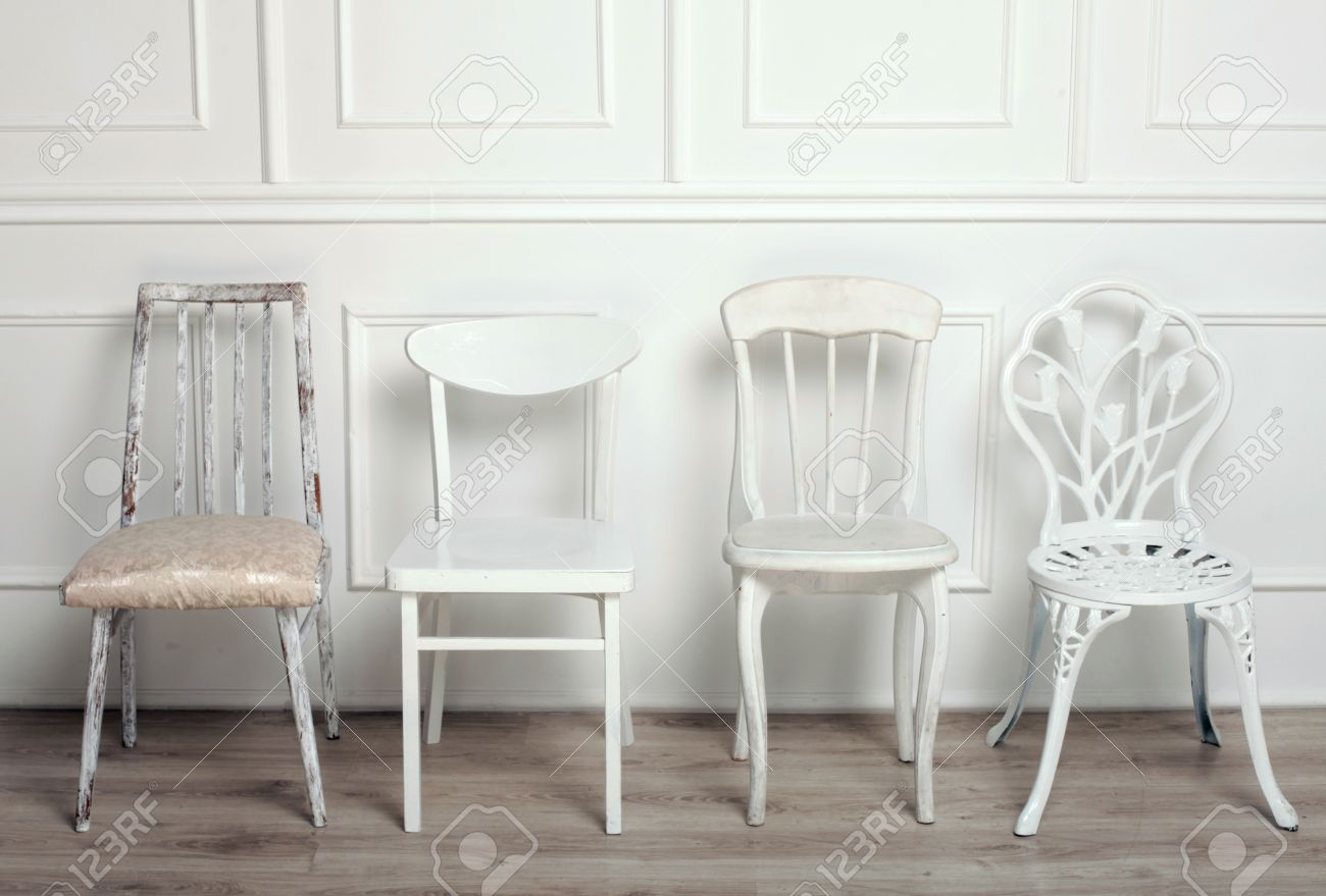 Set of white wooden vintage chairs standing in front of a white ...