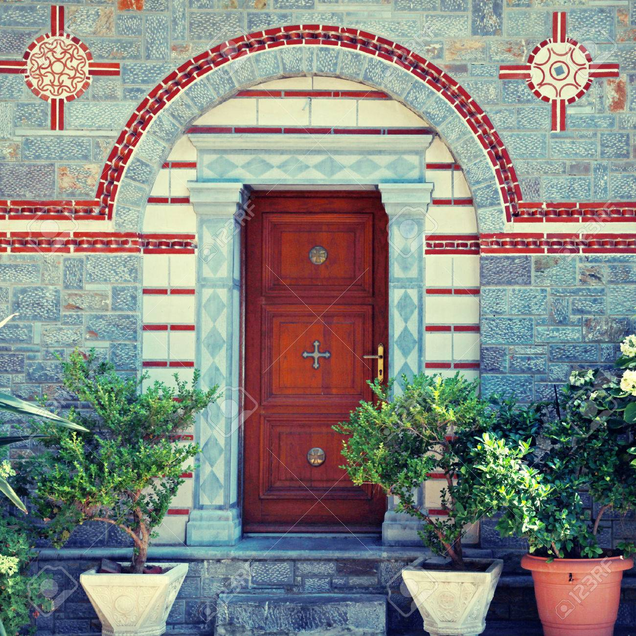 view with ornate front door entrance and flower pots in beautiful