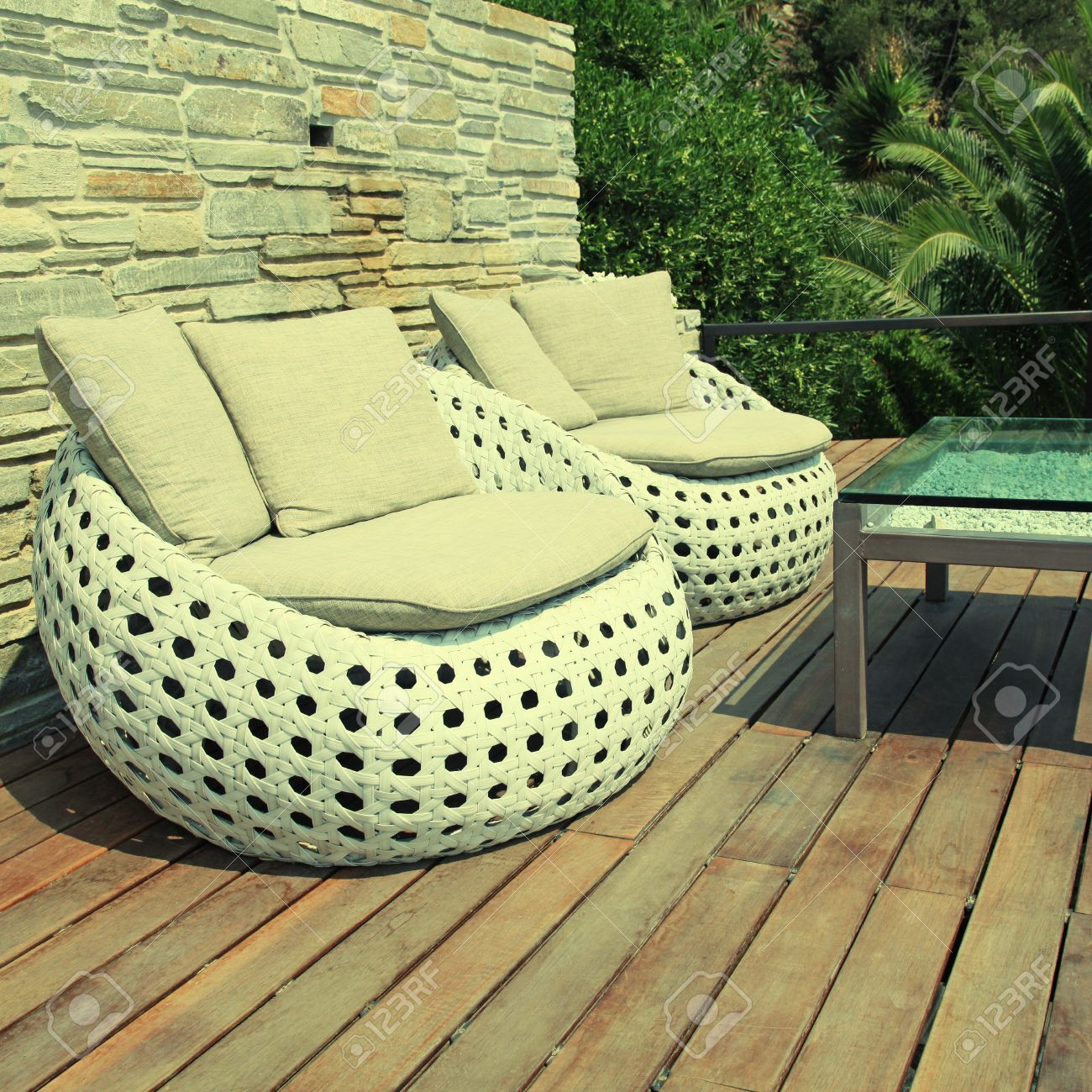 Stock photo white outdoor furniture round rattan armchairs and glass table on wood resort terrace greece square toned image effect