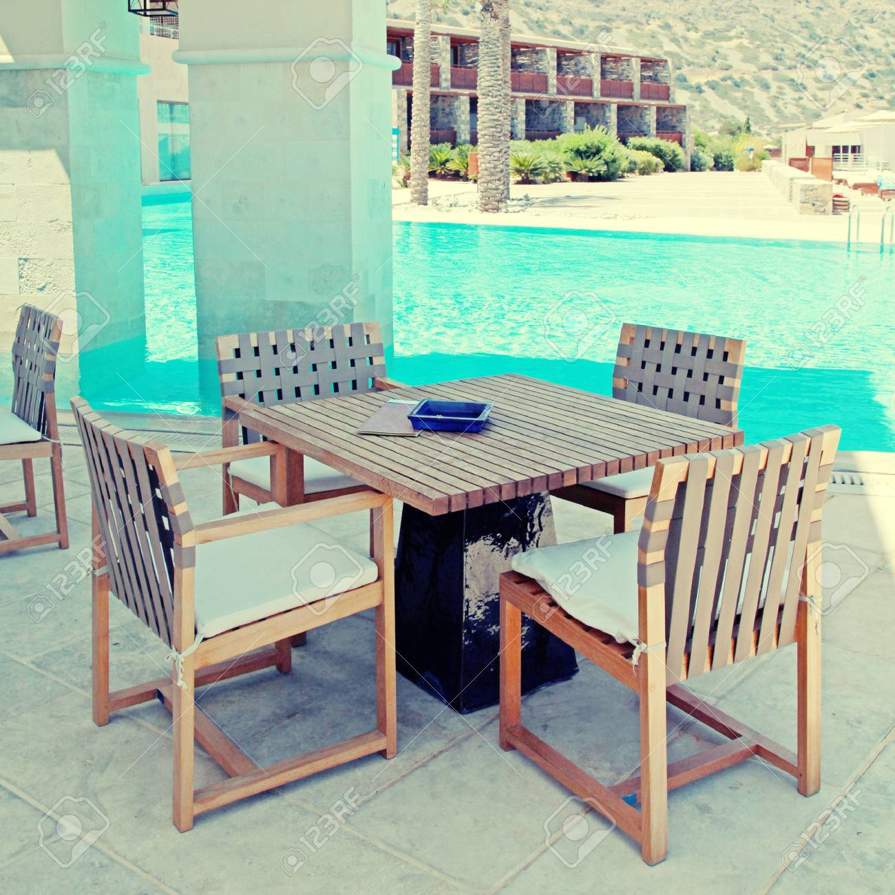 sommer-terrasse des hotels mit pool, outdoor-holz stühle und tisch