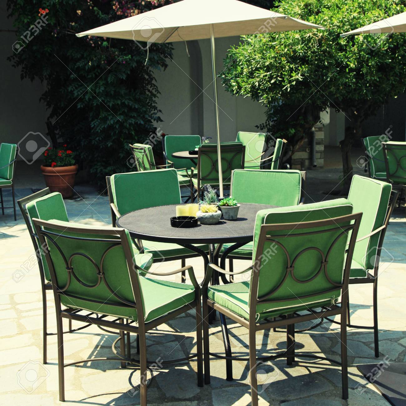 Iron Tables And Chairs With Parasol In Beautiful Mediterranean Patio Cafe.  Square Toned Image,