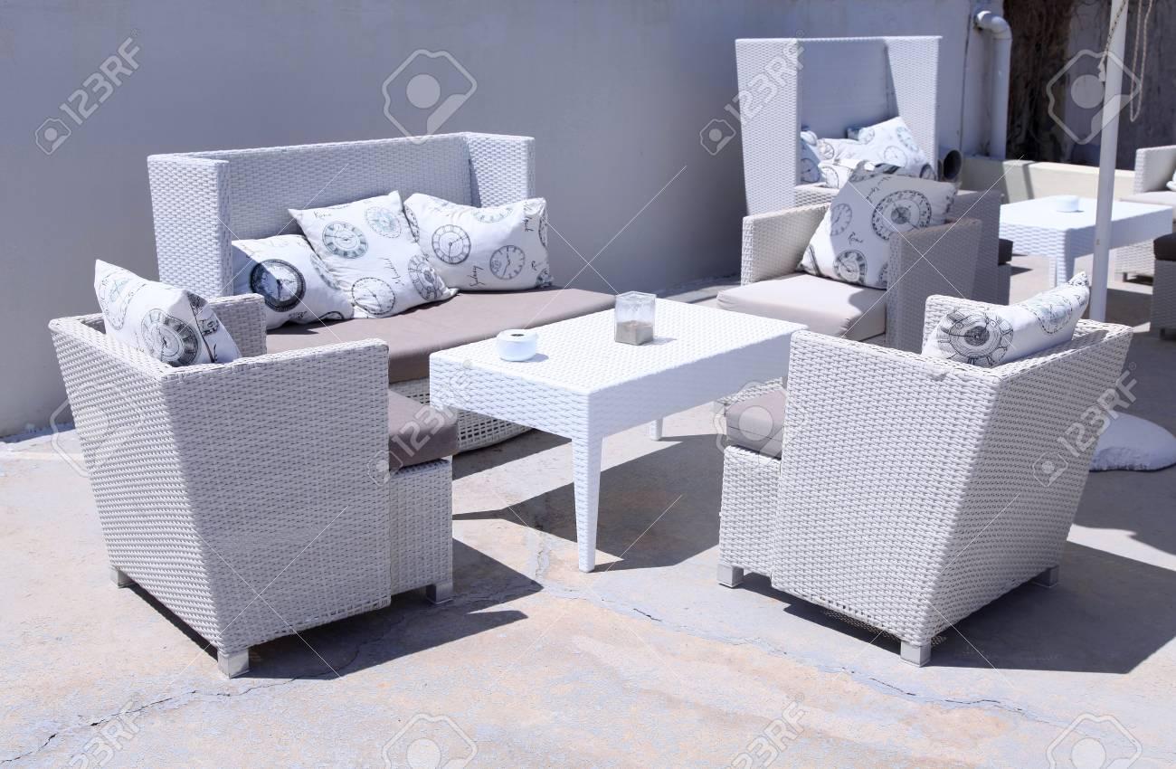 Stock photo white outdoor furniture rattan armchairs on resort terrace greece