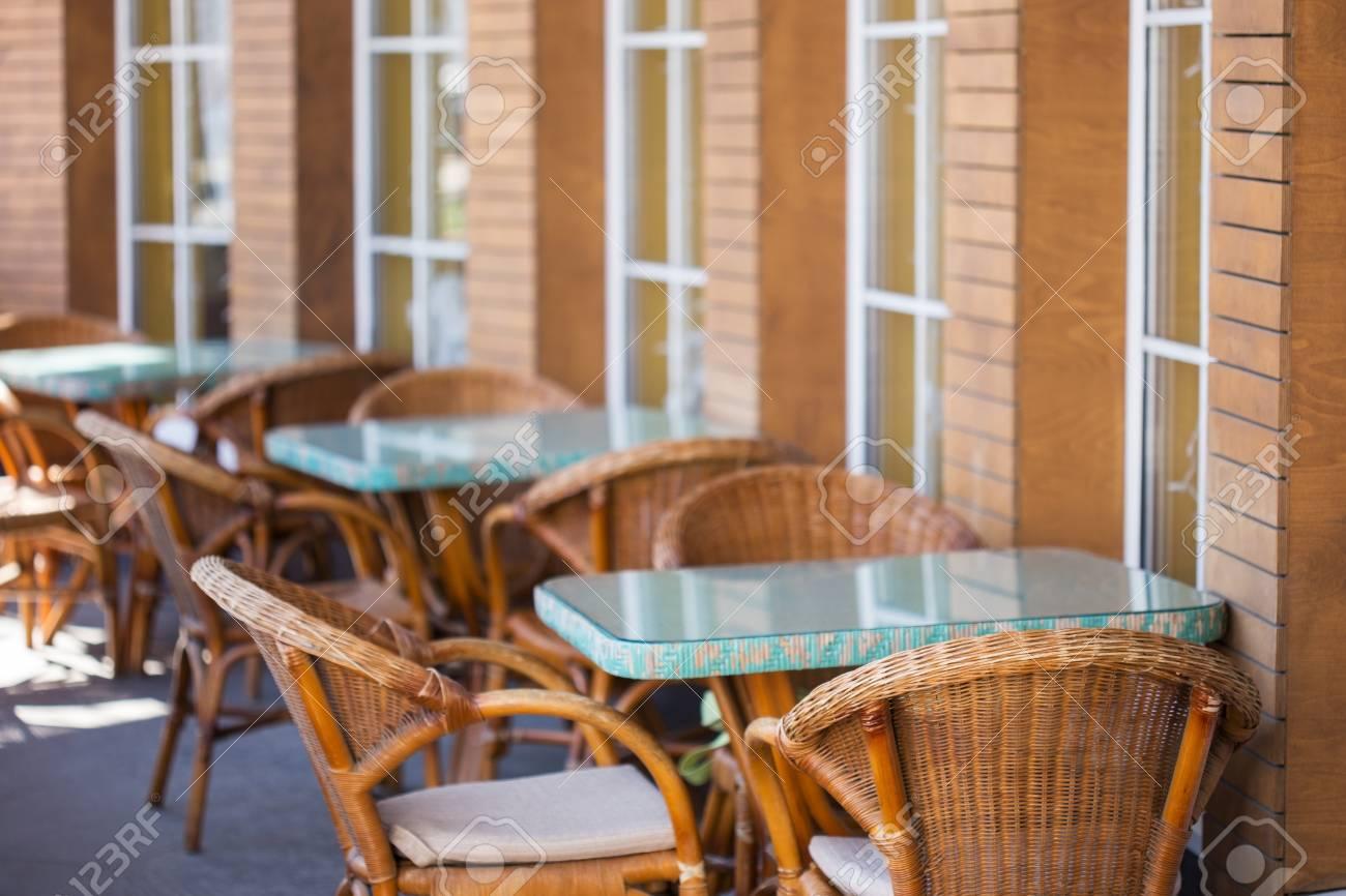 Hermosa Y Acogedora Terraza De Verano Con Sillas De Mimbre Marrón Claro Y Mesas Azules Situadas Frente A Las Ventanas De La Cafetería Dof Superficial