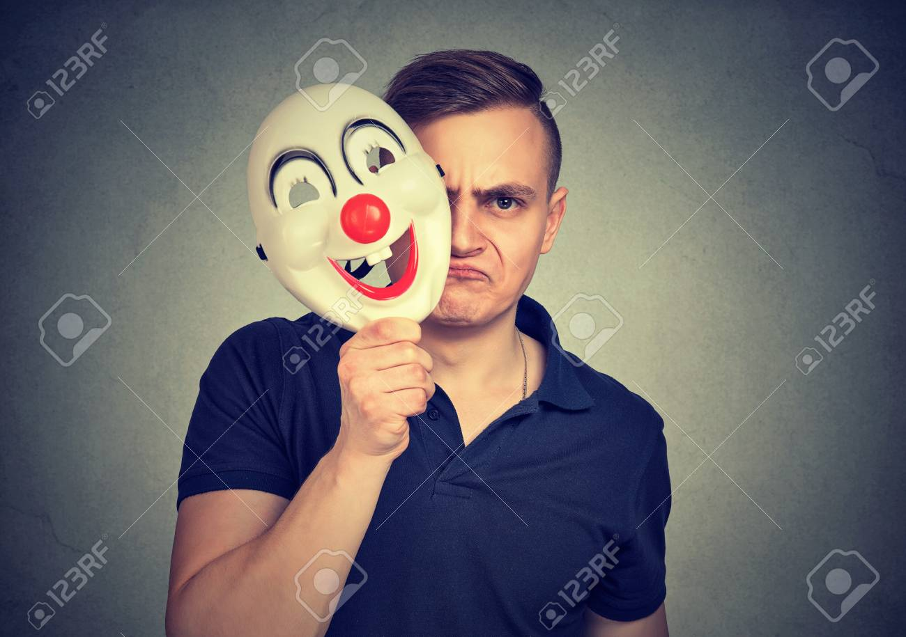 a little mad young negative man hiding real face with clown mask