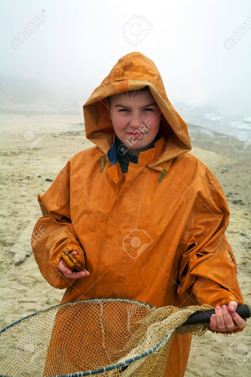 Young amber cather - fisherman smiling standing  by the sea with fisherman's coat on misty day Stock Photo - 5108450