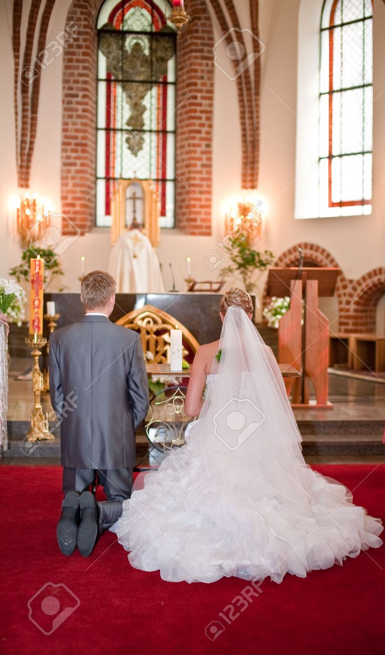 Bride And Groom Kneeling On Wedding Ceremony In Front Of Altar Stock Photo