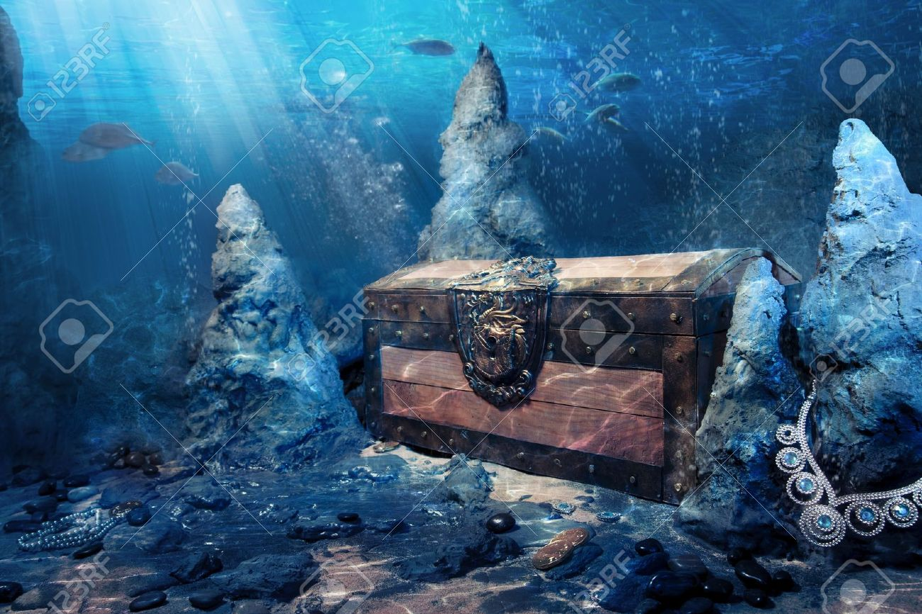 photo of wooden treasure chest submerged underwater with light
