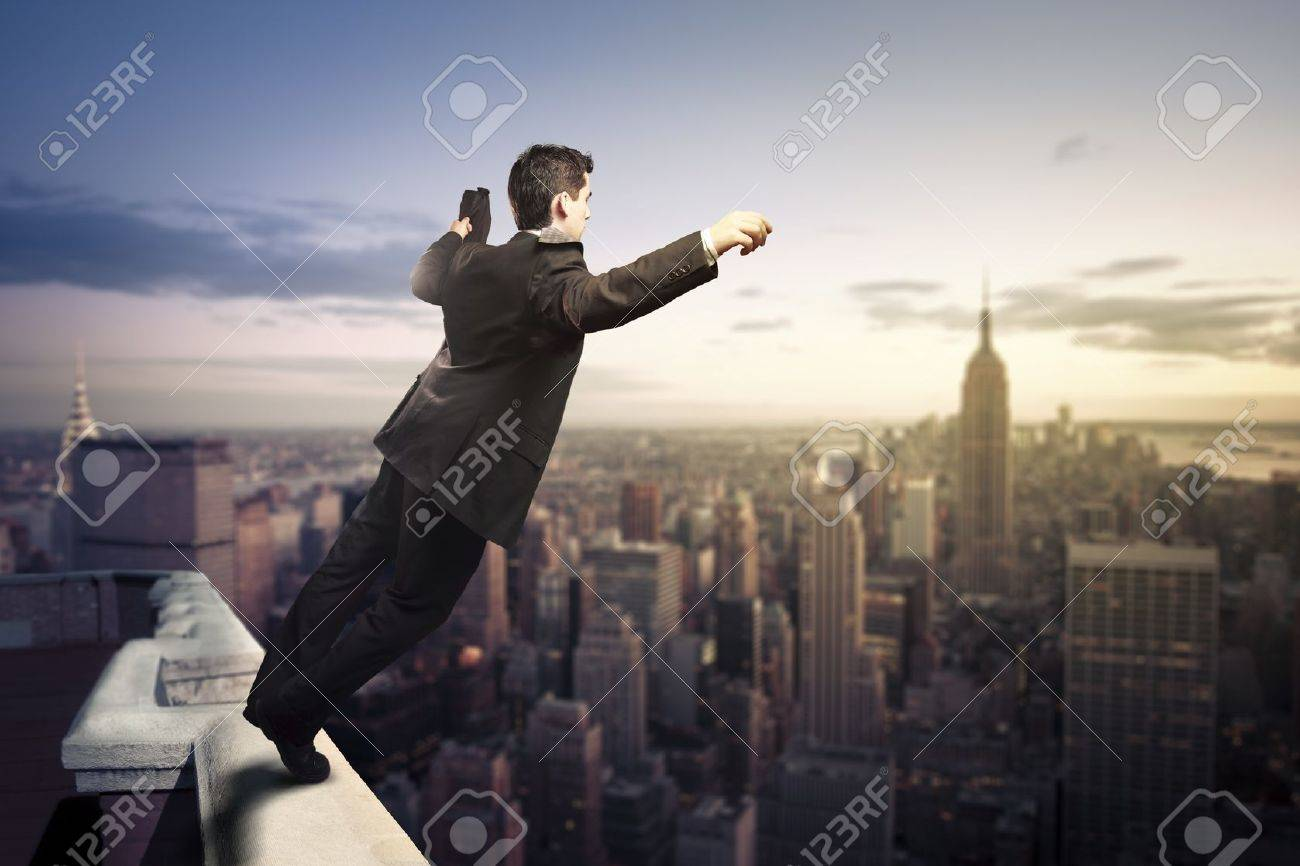 troubled businessman jumping from the top of a building stock photo