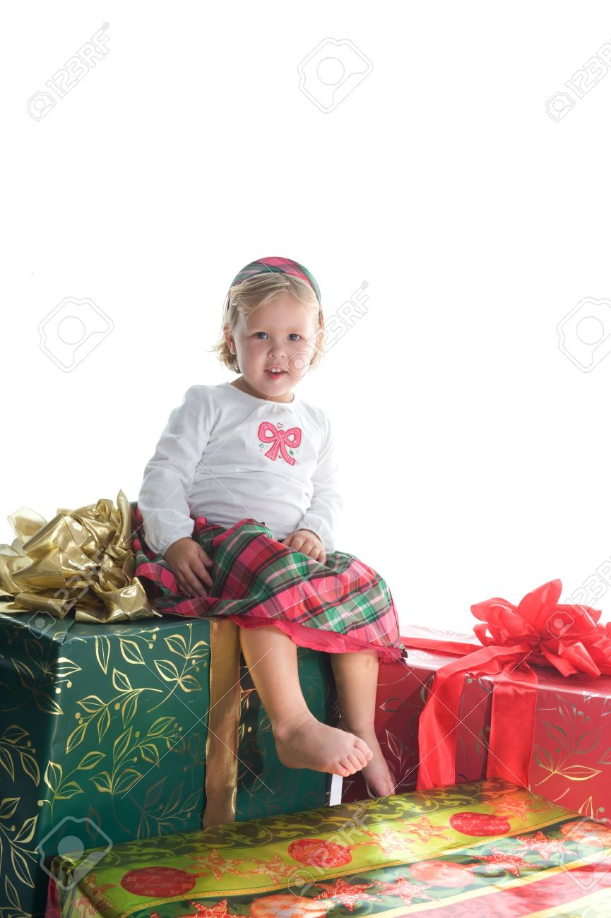 adorable little girl sitting on top of three beautifully wrapped christmas gifts stock photo 5362997