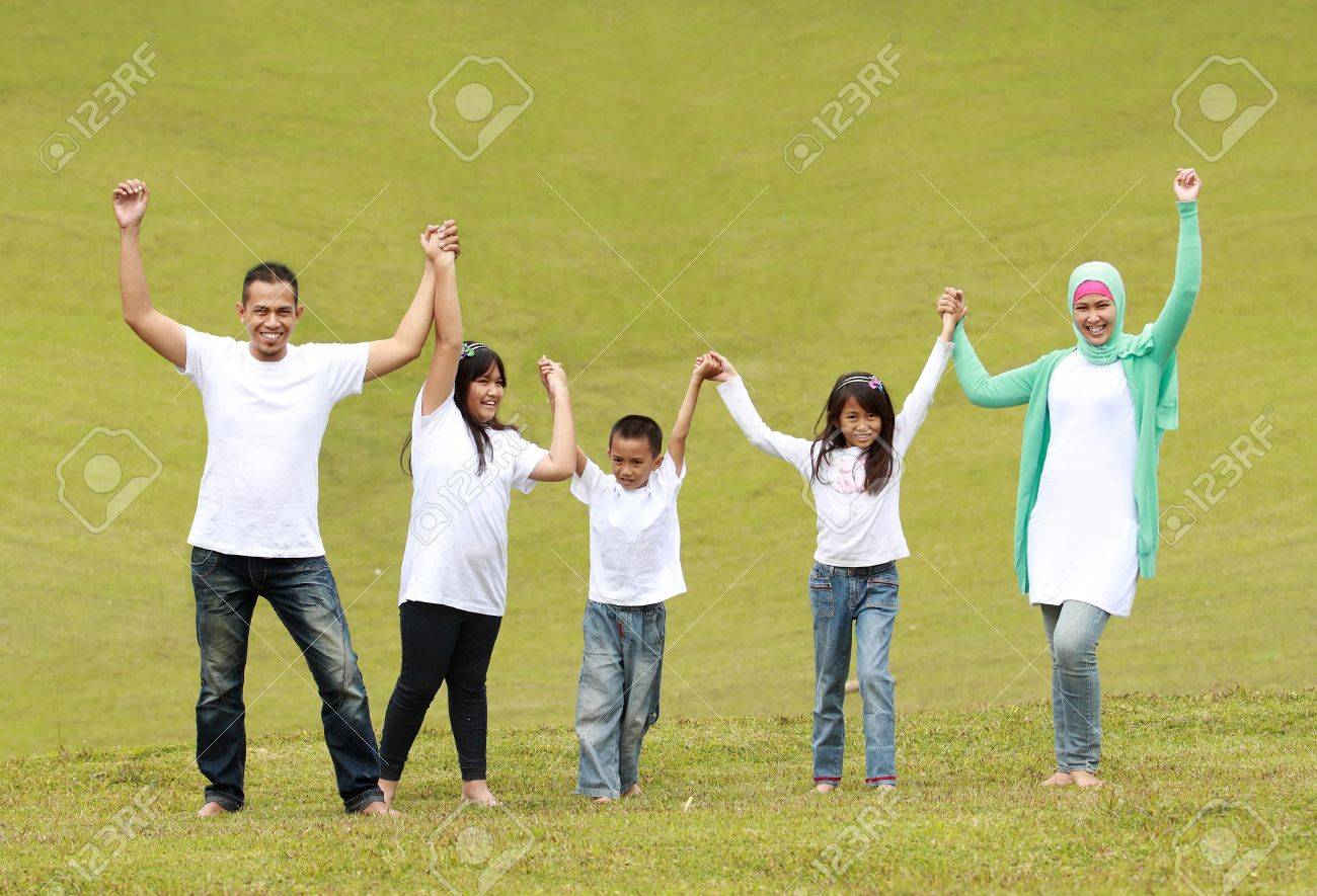 Happy family smiling and raise hand together in the park Stock Photo - 10391343