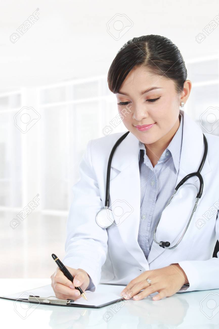 Charming female doctor writing on a clipboard in her office Stock Photo - 11845566