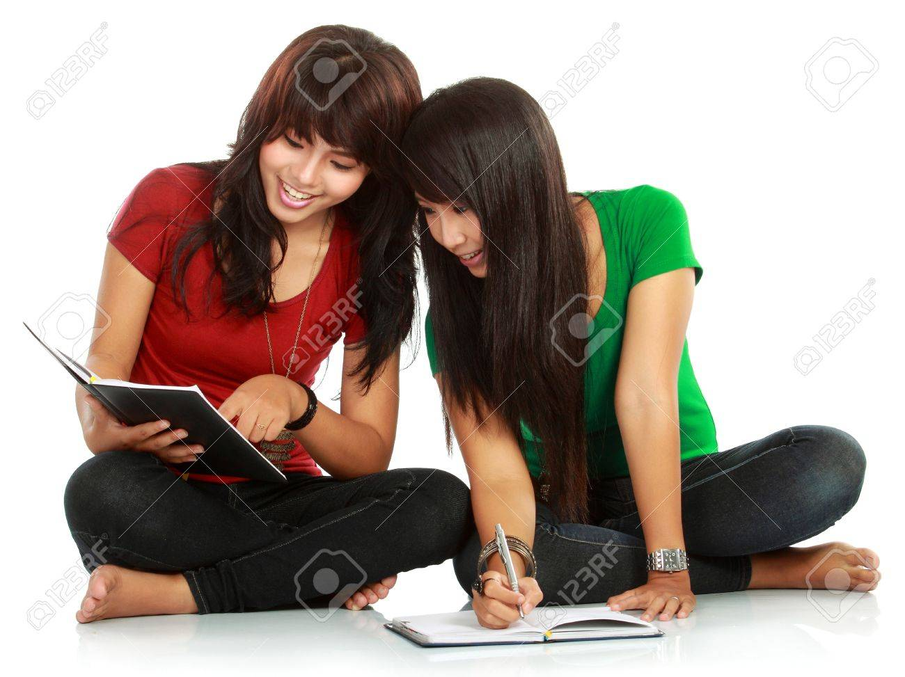 Portrait of a young students smiling while reading a book over white background Stock Photo - 11844988