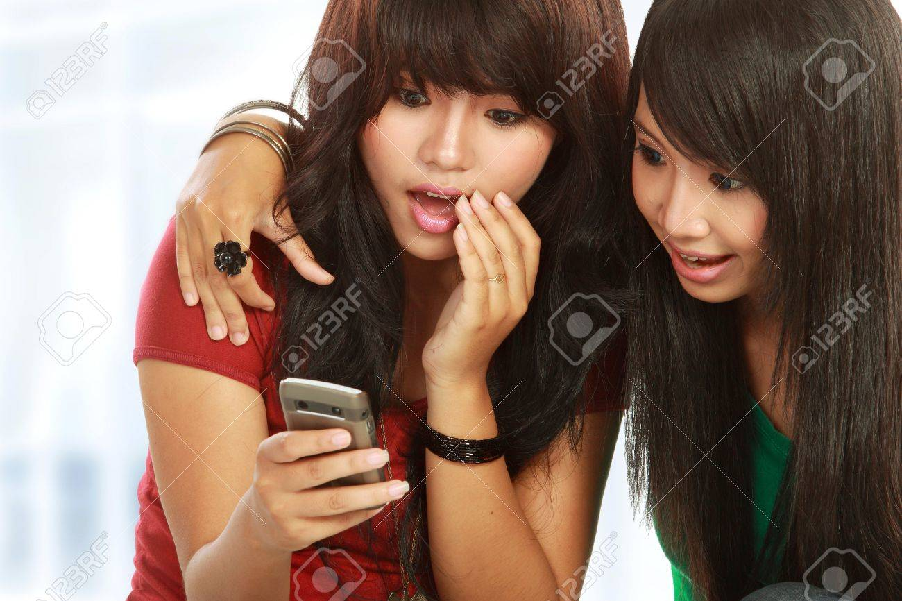 surprised girls reading gossip in mobile phone Stock Photo - 11846830