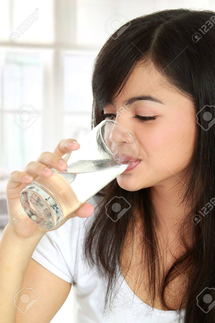 Healthy young woman drinking a glass of water Stock Photo - 12004854