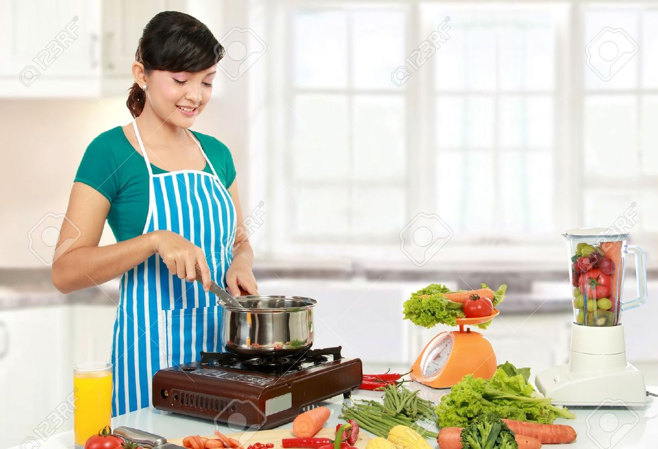 Cooking In The Kitchen | Beautiful Woman Cooking Something In The Kitchen Stock Photo