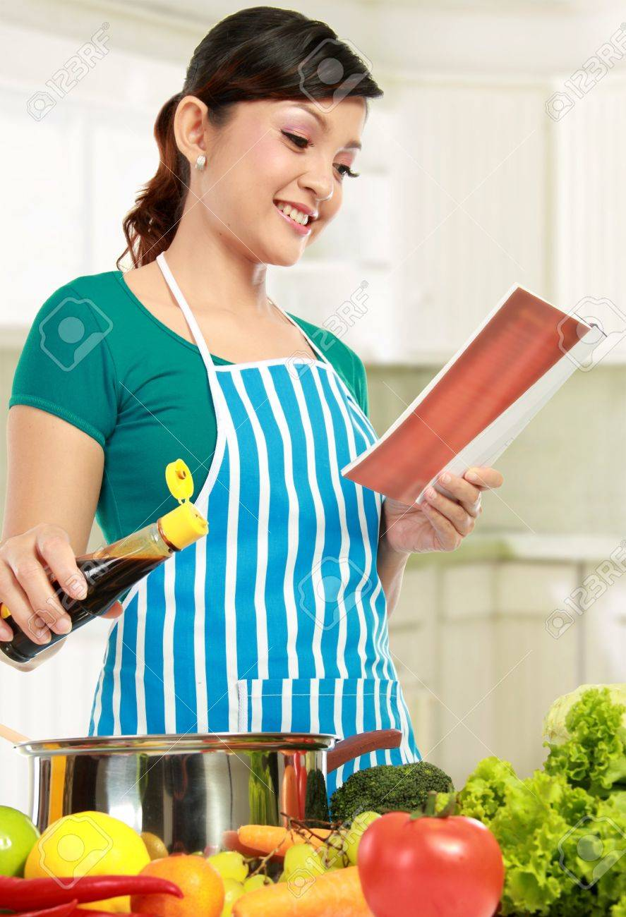 Young Female Looking A Recipe Book While Cooking In The Kitchen ...