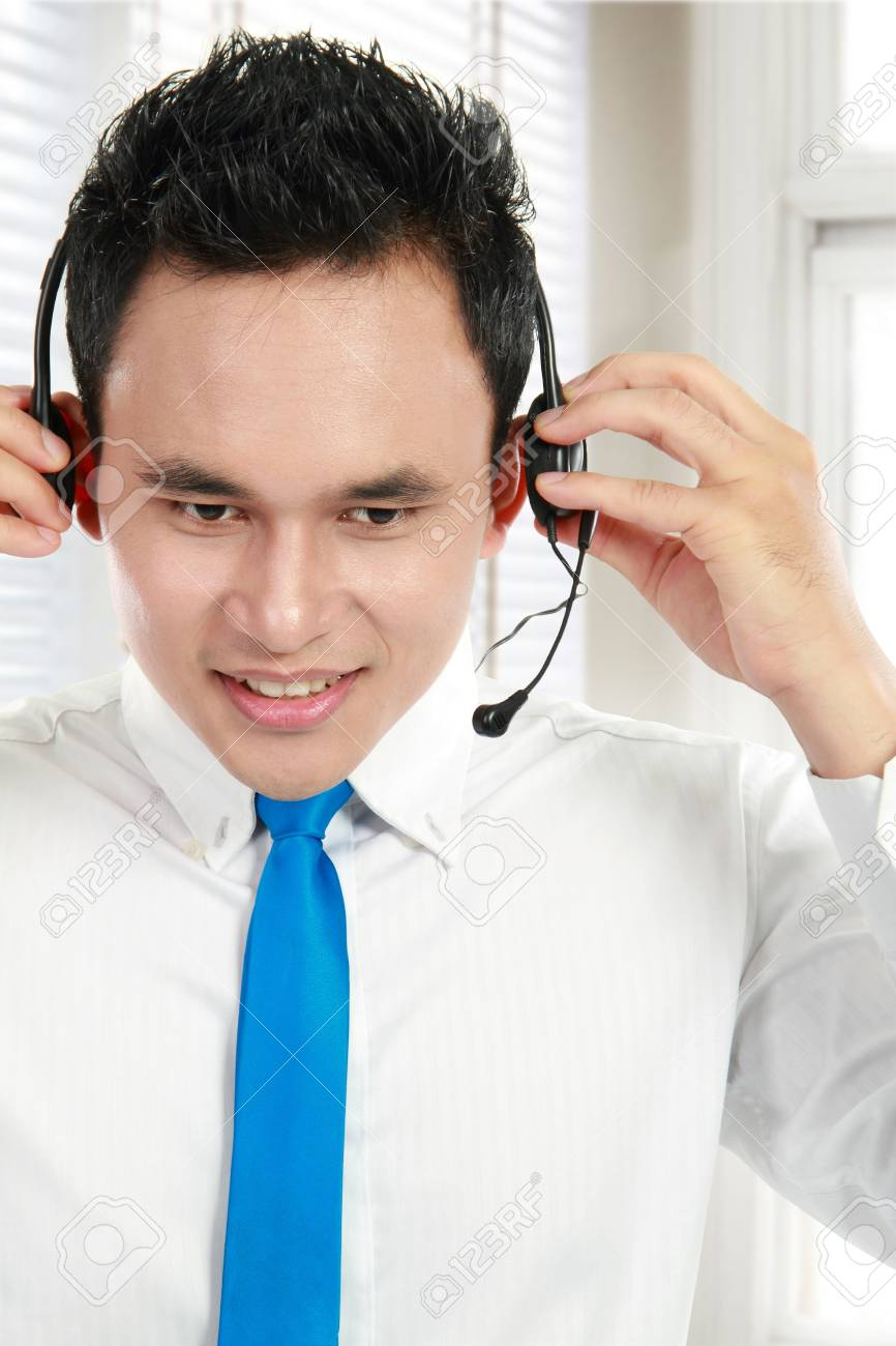 Portrait of a successful asian customer service prepare headset before working Stock Photo - 13157482