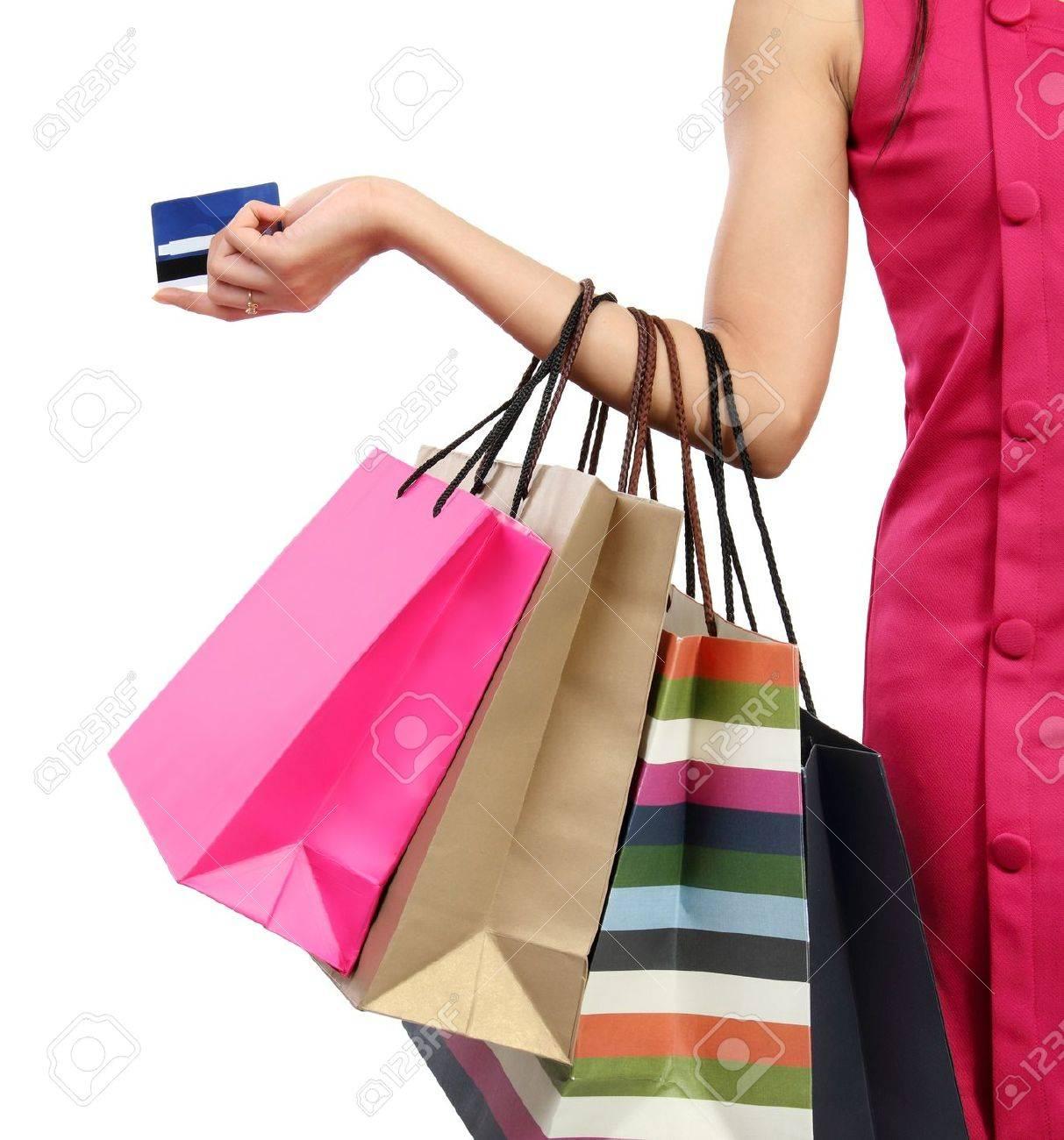 Cerca de mano de la mujer con bolsas de tiendas, comercios y tarjetas de crédito
