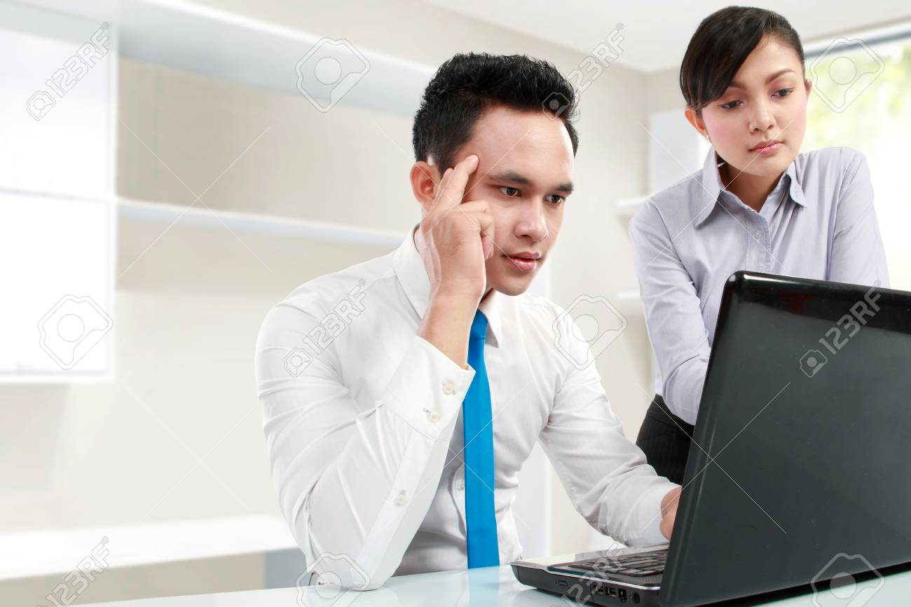 Handsome young business man working on his laptop with female colleague Stock Photo - 13329224