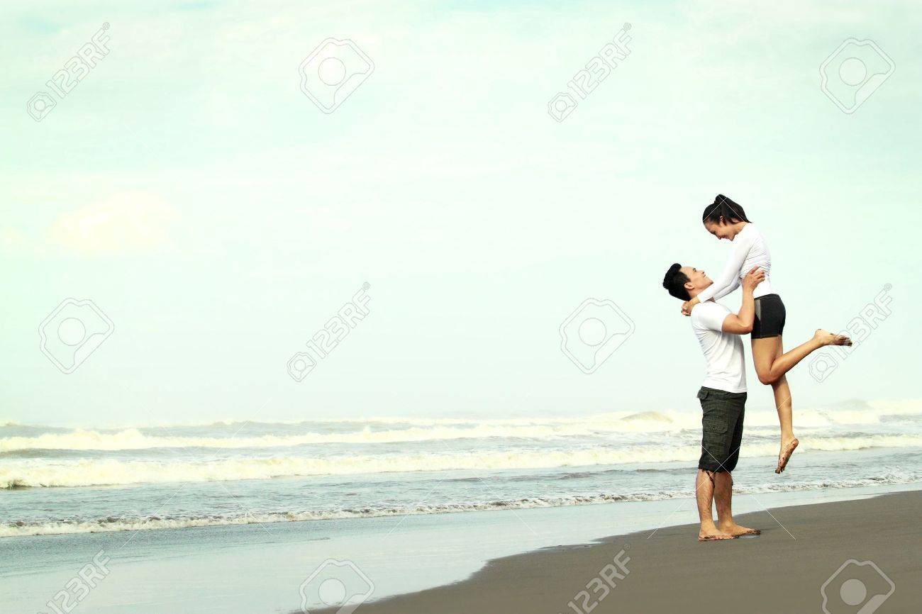 An attractive happy couple having fun on the beach Stock Photo - 13496937